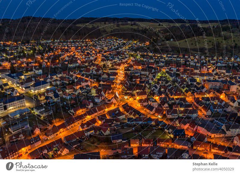 Luftaufnahme über eine beleuchtete Stadt mit Autos an den Straßen und orangefarbenen Lichtern von Laternen und einem Hügel hinter der kleinen Stadt. Nacht