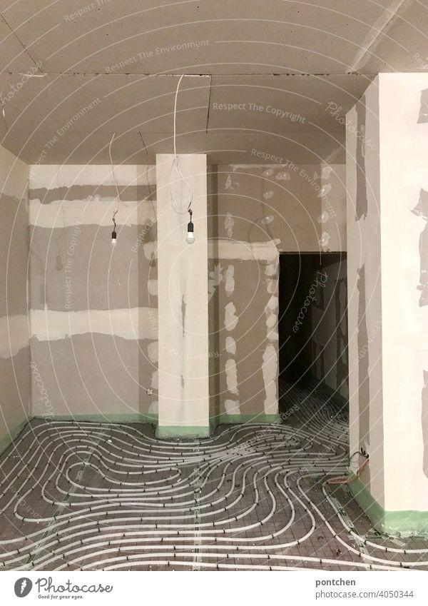 baustelle- ein Ladengeschäft wird saniert. Kernsanierung ladengeschäft renovierung fußbodenheizung malerarbeiten kernsanierung umbau trist leer glühbirnen