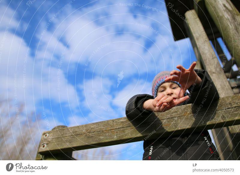 Kind streckt die Hände nach unten Oberkörper Verlässlichkeit Außenaufnahme mehrfarbig Hilfsbereitschaft Geborgenheit Schutz Sicherheit Vertrauen Mut