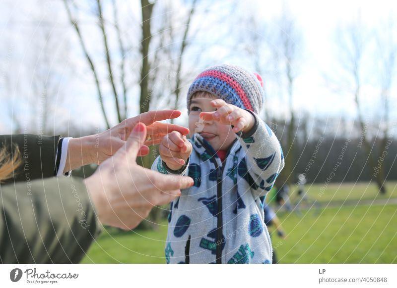 kleines Kind streckt die Hände nach seiner Mutter aus Wegsehen Oberkörper Verlässlichkeit Außenaufnahme mehrfarbig Hilfsbereitschaft Liebe Zusammensein