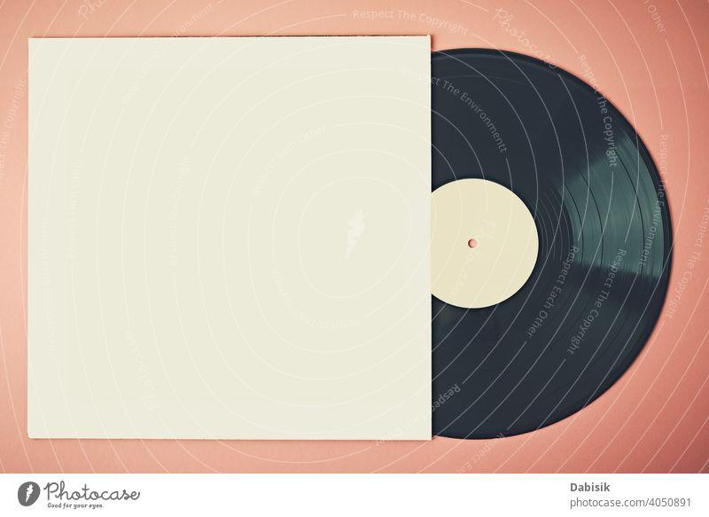 Alte Retro-Vinylscheibe in Papierhülle auf rosa Hintergrund, Mockup. Vintage getöntes Foto Scheibe Aufzeichnen Musik retro Fall altehrwürdig Audio Entertainment