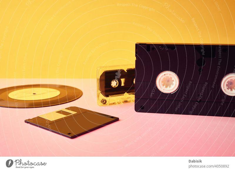 Vinyl-Disc, Floppy-Diskette, VHS und Bandkassette auf gelbem Hintergrund. Retro und Nostalgie Konzept retro Scheibe Kassette Aufzeichnen altehrwürdig Musik
