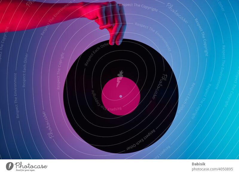 Hand halten Retro-Vinylscheibe mit Neon-Hintergrund Scheibe neonfarbig retro Musik Aufzeichnen altehrwürdig Audio Entertainment Klang stereo Melodie Lamelle