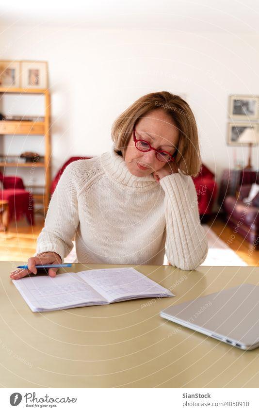 Senioren mittleren Alters, die zu Hause am Computer arbeiten Frau Laptop reif Menschen eine Person Lifestyle Schreibtisch benutzend trinken Brille attraktiv