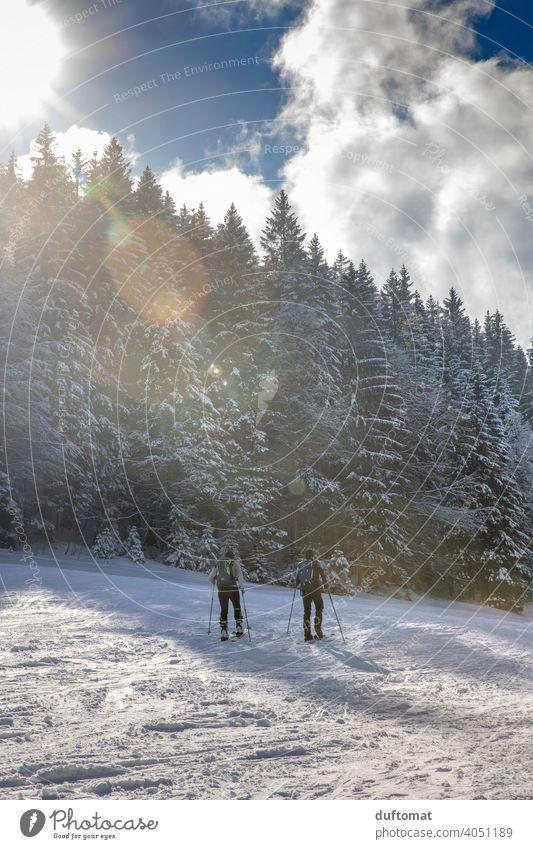Tourengänger in Winterlandschaft mit Bergen Sport tourengehen Ski Berge u. Gebirge Bergsteiger Schnee beschneit winterlich sportlich draußen zwei lens flair