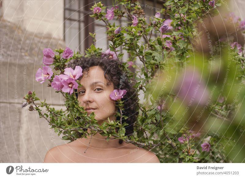 Beauty Headshot einer jungen brünetten Frau mit rosa Blumen im Freien. Gedreht auf analogem 35-mm-Schmalfilm. posierend Model Person schön Schönheit frisch