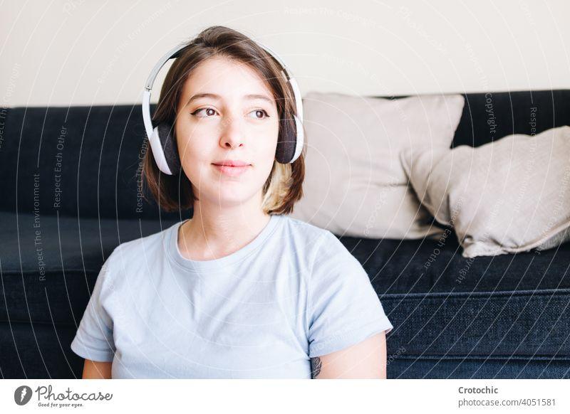 Lächelndes Mädchen schaut nachdenklich, während es Musik hört Person Frau Teenager hören besinnlich jung Blick Glück zuhören Freude Kaukasier im Innenbereich