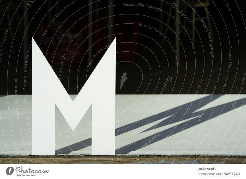 konform|Buchstabe M Großbuchstabe Schaufenster Sonnenlicht Schattenspiel Typographie Silhouette Hintergrund neutral einzeln Glasscheibe doppel