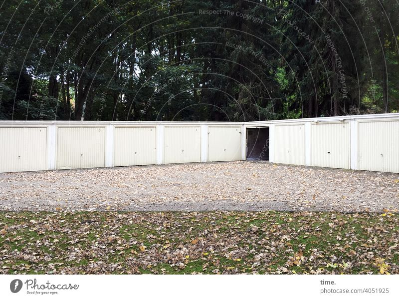 schwarzes Loch Garage Garagentor verschlossen offen Kies Platz wiese laub herbstlaub wald bäume menschenleer