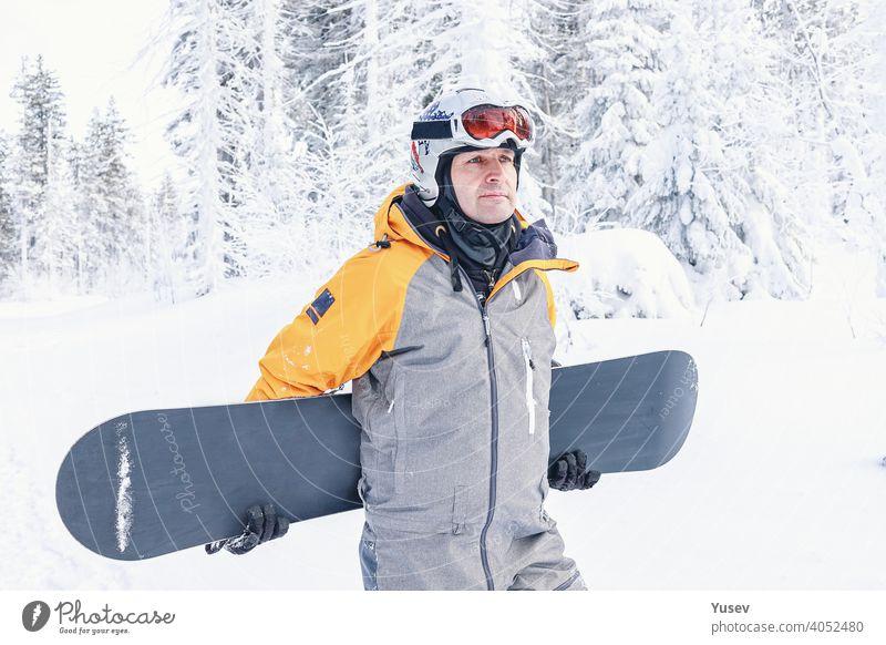 Schöne kaukasische Mann in einem hellen gelben und grauen Overall, weißen Helm und Brille hält sein Snowboard. Wintersport, Freizeitbeschäftigung. Urlaub in den Bergen. Vorderansicht.