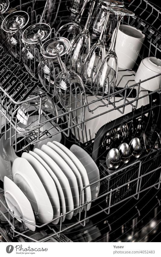 Kristall sauber glänzende Teller und transparente Gläser in einer Spülmaschine. Geschirr, Küche, Hausarbeit. Nahaufnahme. Vertikale Aufnahme. Kristalle