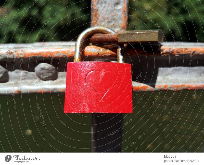 Rotes Liebesschloss mit Herz als Gravur an einem rostigen Brückengeländer an einer Brücke über die Bega in Lemgo bei Detmold in Ostwestfalen-Lippe Treue