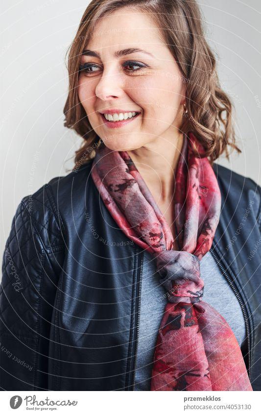 Junge, schöne, lächelnde Frau mit Seidenschal um den Hals und Lederjacke, die wegschaut und vor einem schlichten Hintergrund steht Schal Person Model Porträt