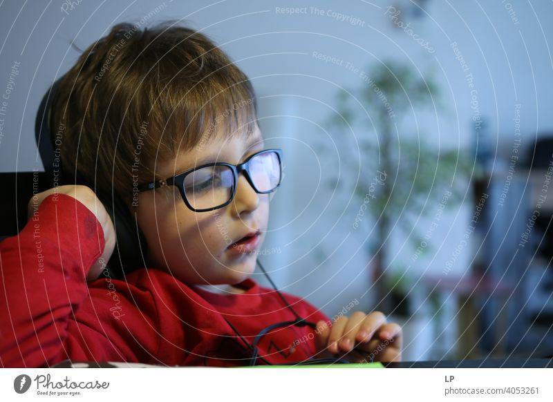 Kind trägt eine Brille und hört einen Kopfhörer Sicherheit Seuche Quarantäne zuhören Musik Familienzeit Musik hören Technik & Technologie Vernehmung Erholung