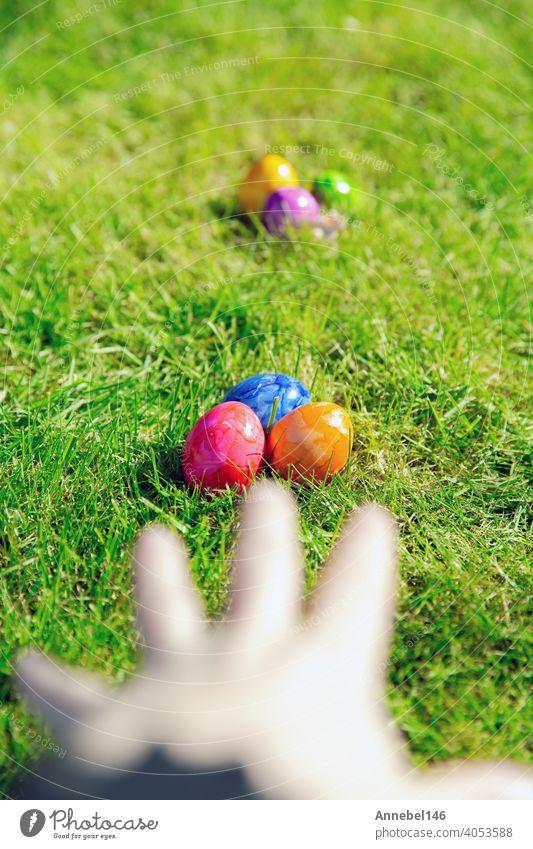 Ostereier im Gras versteckt, bunte handgemachte gemalt Ostereier jagen, Happy Easter Holiday Konzept im Garten oder Park, Ostern Frühling Ei Feiertag farbenfroh