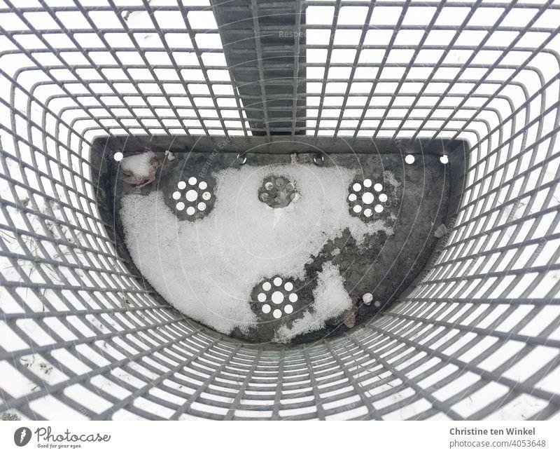 Blick von oben in einen verschneiten leeren Abfallkorb aus Metallgitter mit gestanztem Blümchenmuster am Boden Mülleimer Schnee kalt Muster Umwelt Winter