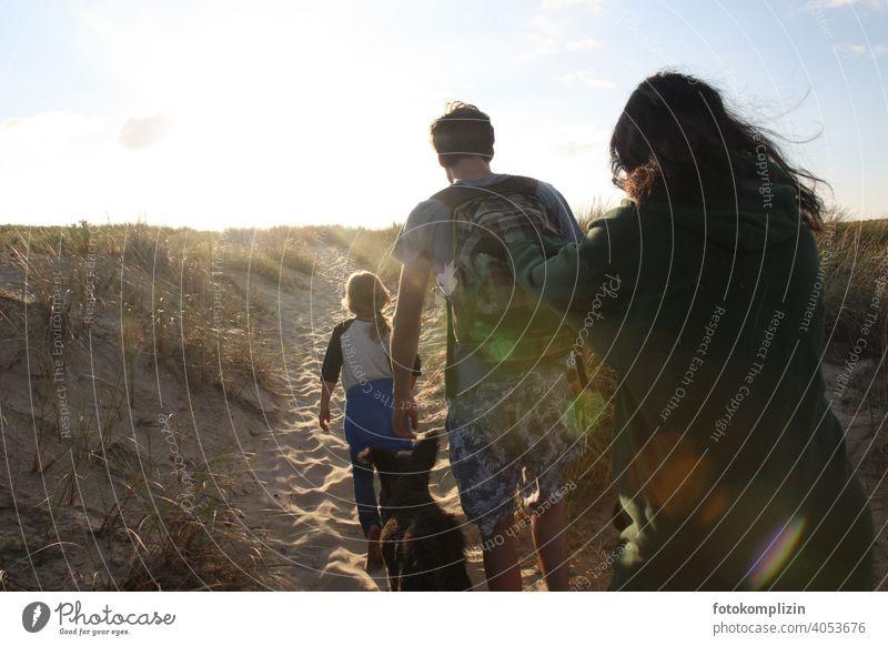 Mann, Frau und Kind mit Hund auf dem Weg über die Düne zum Strand Ferien & Urlaub & Reisen Familienurlaub Zusammensein Erholung Sand Familienzeit Auszeit