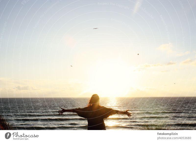 junge Frau mit ausgebreiteten Armen vor Sonnenuntergang am Meer Harmonie Lebensfreude Freiheit Fernweh Leichtigkeit Unendlichkeit Individualität Gesundheit
