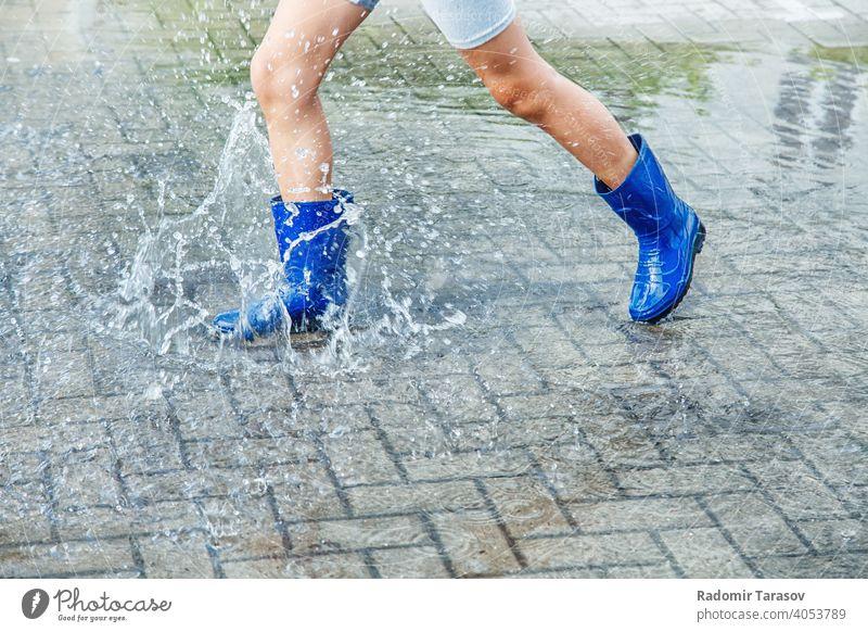 Mädchen in blauen Gummistiefeln springt in eine Pfütze nach einem Regen Herbst Stiefel Wasser Saison nass Wetter Spaziergang Spaß Kind im Freien Beine Straße