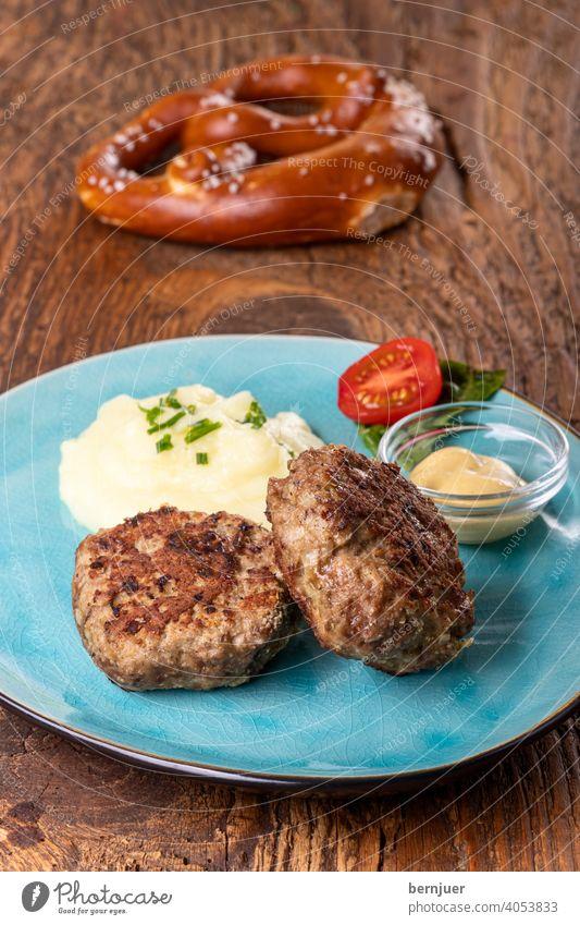 zwei Fleischpflanzerl einem Teller bulette senf kartoffelpüree kartoffelbrei breze brezel bayerisch rustikal deftig holz tomate snack brotzeit hackfleisch