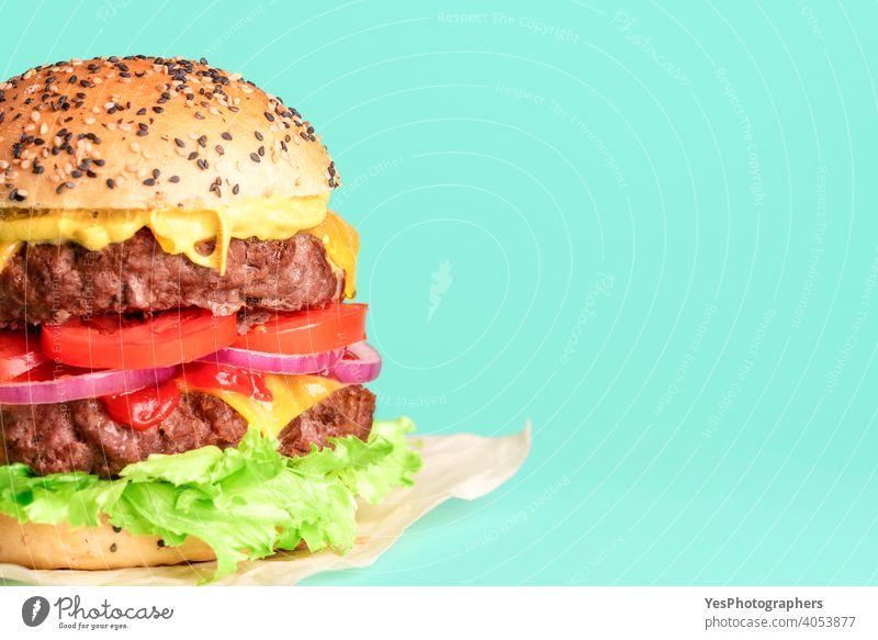 Hamburger Seitenansicht Nahaufnahme isoliert auf einem grünen Hintergrund. Barbecue Rindfleisch groß Brot Brötchen Burger Cheddar Käse Cheeseburger farbig