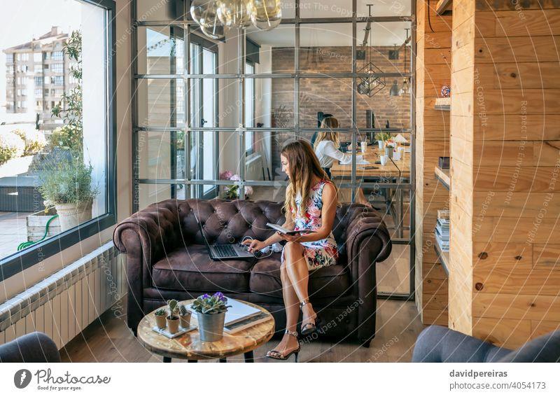 Geschäftsfrau arbeitet mit Laptop auf dem Sofa sitzend arbeiten Chester-Sofa konzentriert Coworking-Büro elegant Frau Sandalen mit Absatz jung Liege Computer