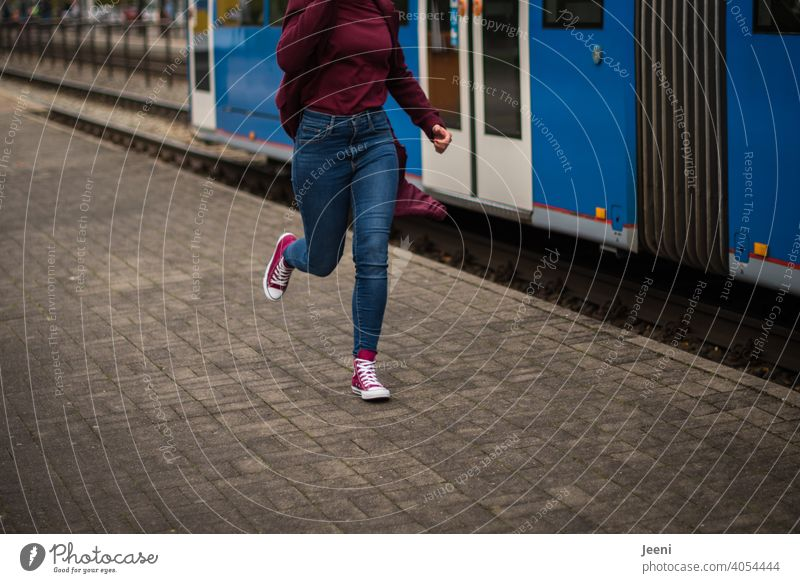 Der Zug ist abgefahren | Eine Frau rennt einer abfahrenden Straßenbahn hinterher Junge Frau 20-24 Jahre 25-29 Jahre 30-45 Jahre Mädchen Jugendliche rennen