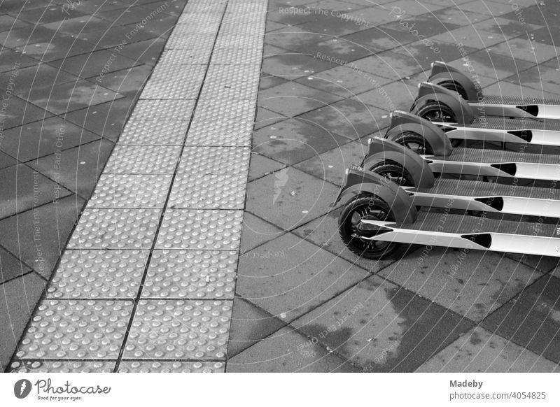 E-Roller aufgereiht zur Vermietung neben einem taktilen Leitsystem für Sehbehinderte auf grauem Straßenpflaster in der Innenstadt von Frankfurt am Main in Hessen, fotografiert in neorealistischem Schwarzweiß