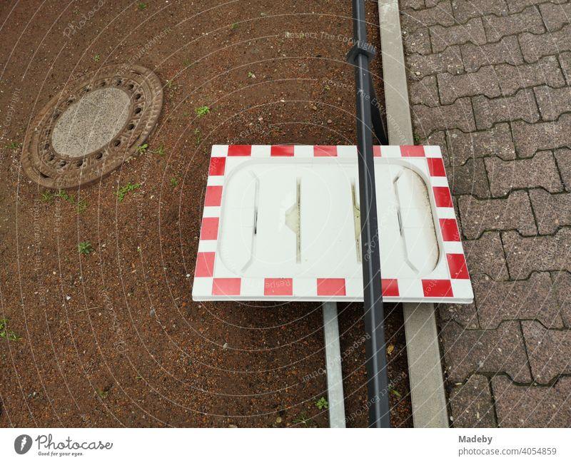 Rahmen eines Verkehrsspiegel in Rotweiß ohne Spiegel als Stillleben mit Gullydeckel am Straßenrand im Stadtteil Bockenheim in Frankfurt am Main in Hessen
