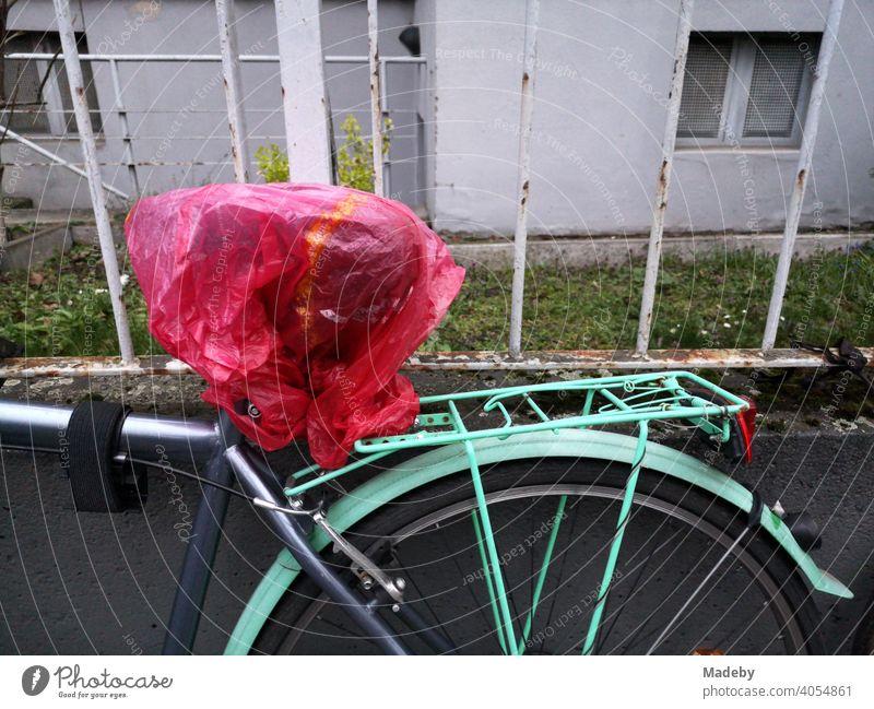 Fahrrad in Grau und Türkis mit transparenter roter Plastiktüte über dem Sattel vor einem alten Eisenzaun im Nordend von Frankfurt am Main in Hessen Rad Stadtrad