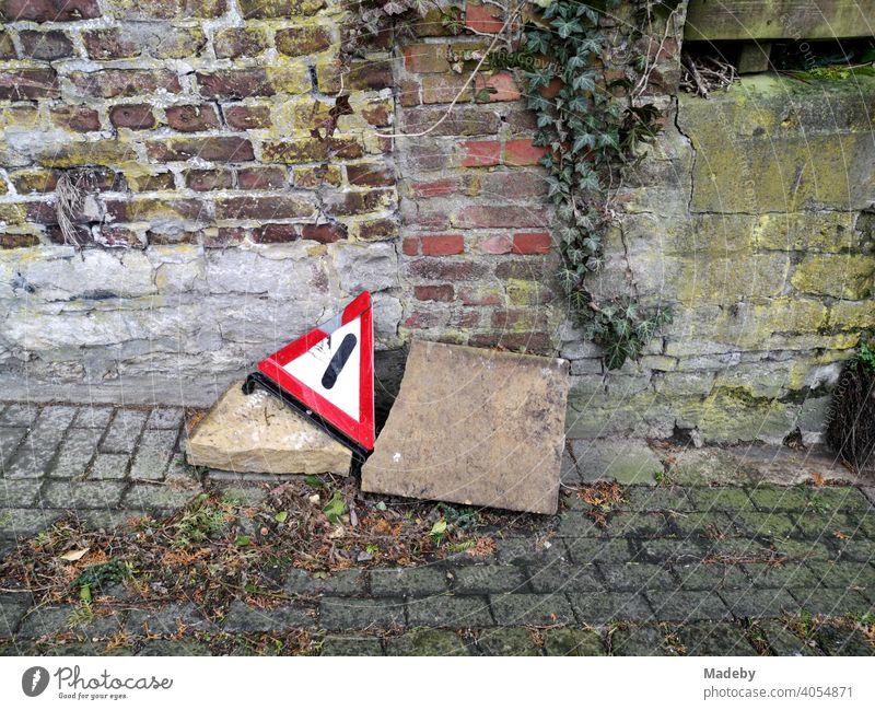 Kaputtes Warndreieck mit großen Steinen am Straßenrand auf altem Kopfsteinpflaster vor Mauerwerk im Herbst in der Altstadt von Oerlinghausen bei Bielefeld im Teutoburger Wald in Ostwestfalen-Lippe