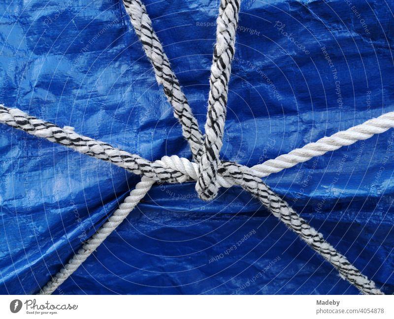 Weißes und schwarzweißes Schiffstau als Stillleben auf einer blauen Plane über einem Boot auf einem Anhänger in Oerlinghausen bei Bielefeld im Teutoburger Wald in Ostwestfalen-Lippe