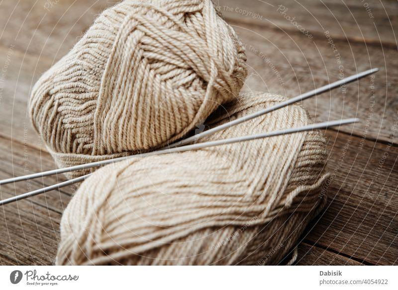 Zwei Stränge Wollgarn und Nadeln zum Stricken auf einem hölzernen Hintergrund stricken Wolle Garn Wollstoff Strang Handarbeit handgefertigt Hobby Faser Handwerk