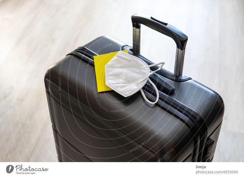 Ein Koffer mit einem gelben Impfpass und eine weiße FFP2 Maske Reise ffp2-maske covid-19 Coronavirus Mundschutz Schutz Urlaub Prävention Schützen