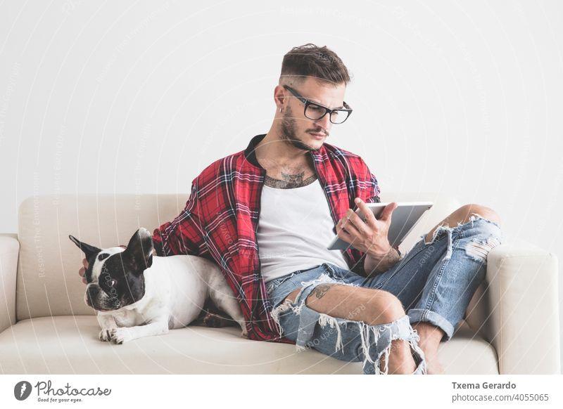 Junge Hipster Blick auf sein Tablet neben seinem Hund sitzt auf dem Sofa französische Bulldogge Piercing durchbohrt Hut Ohrringe Hemd Vollbart Haustier Welpe