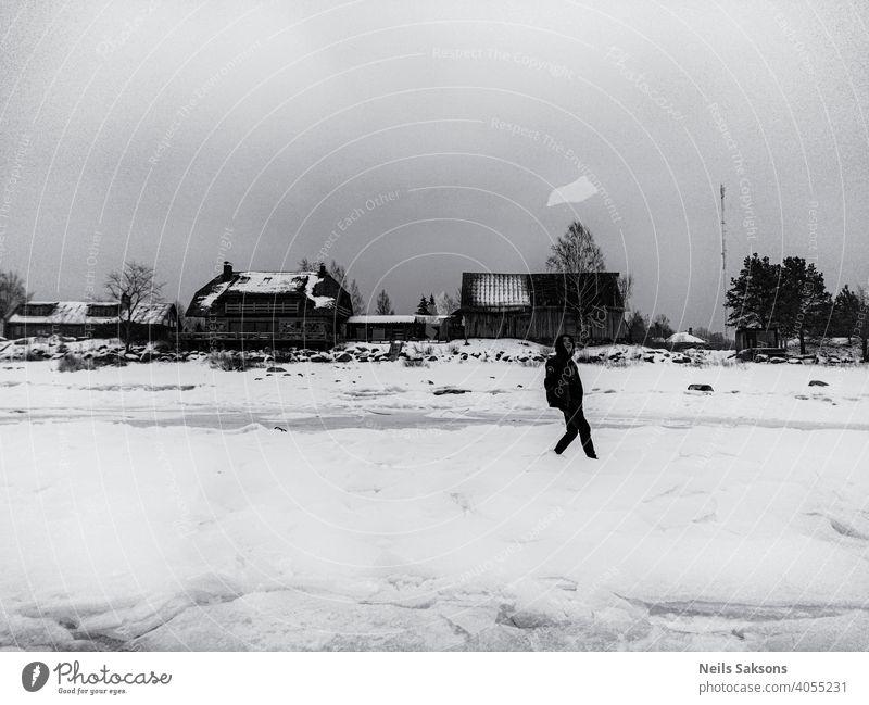 Junge, der ein Stück Eis auf dem Ostseeeis aufwirft Winter Person werfen Werfen MEER Haus Meeresufer Wasser Urlaub Freude freudig Spaß schwarzes Kleid