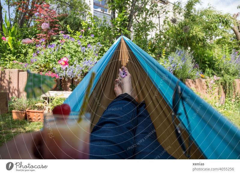 Urlaub im Garten mit leckerem Drink in der Hand und Füßen in der Hängematte; Entspannung pur Pflanzen Blumen privat Pause Erholung Sonnenbrille Sommer