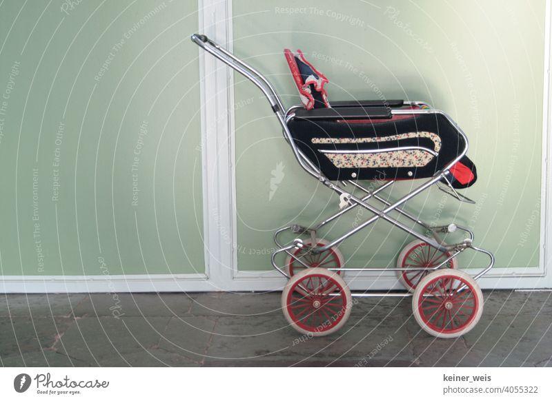 Ein alter Puppenwagen erinnert an Kindheit in den siebziger Jahren voller Trauer und Trostlosigkeit puppenwagen Kinderwagen Hausflur Spielzeug Tag