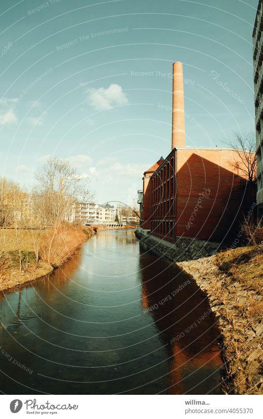 Ein sonniger Tag am ruhigen Fluss, an dessen Ufer eine Fabrik mit Schornstein steht. Time meint, die kleinen Wölkchen sollten auch erwähnt werden.