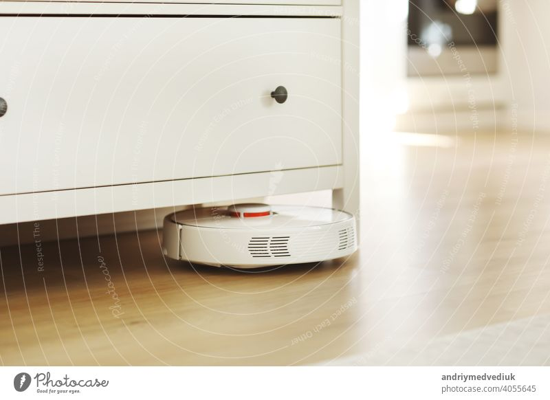 Weißer Roboter-Staubsauger auf Laminatboden Reinigung Staub im Wohnzimmer Interieur. Intelligente elektronische Haushaltstechnik. smart home Raumpfleger