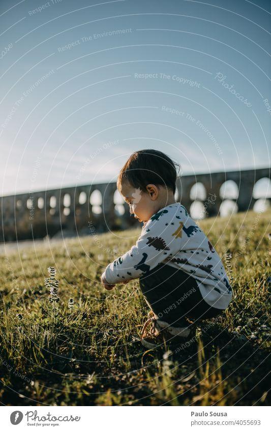 Seitenansicht Kind spielt im Freien Kindheit 1-3 Jahre Kaukasier erkunden authentisch Frühling Frühlingsblume Fröhlichkeit Kleinkind Glück Außenaufnahme Natur