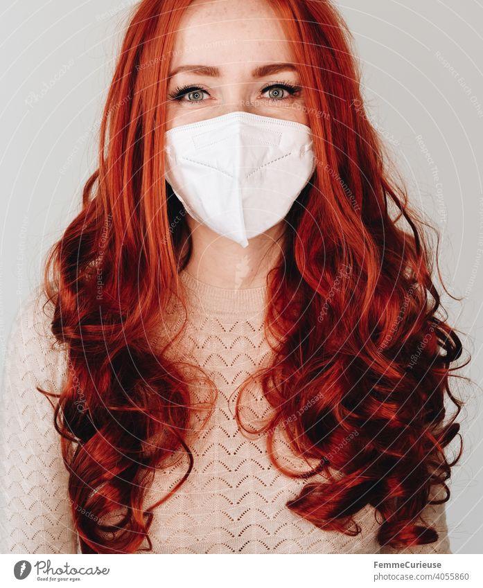 Frau mit langen roten lockigen Haaren und FFP2 Maske Schutzmaske schaut in die Kamera mit lächelnden Augen - Portrait Lächeln ffp2 rote Haare lange Haare