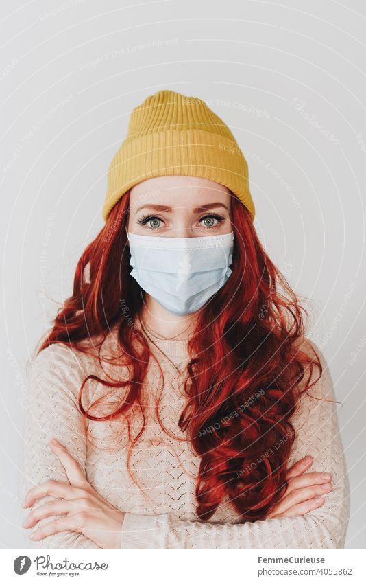 Frau mit roten langen lockigen Haaren und gelber Hipster Beanie Mütze trägt medizinische Schutzmaske Maske Mundschutz und schaut in die Kamera