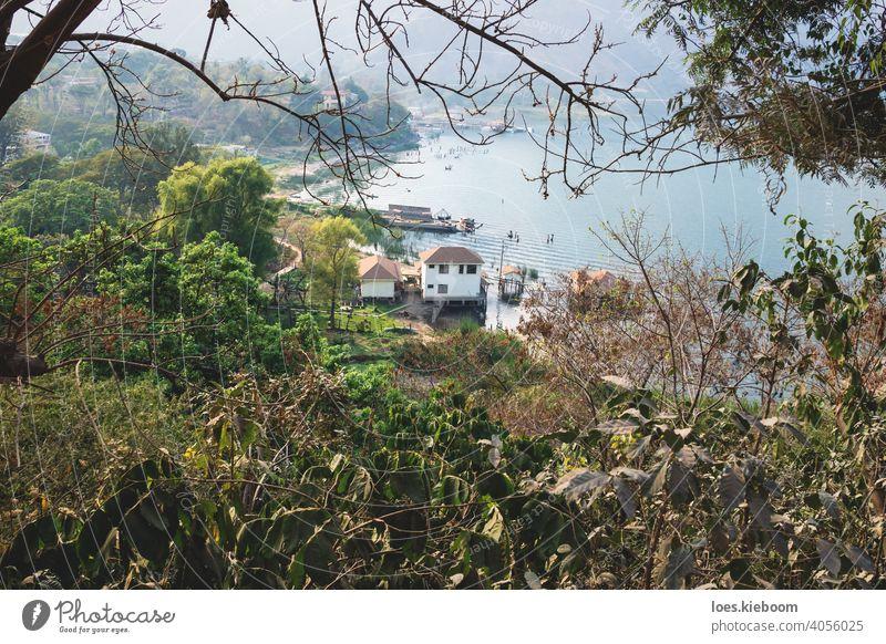 Blick von oben auf die Dorfküste entlang des Atitlan-Sees durch Bäume, San Juan la Laguna, Guatemala Küste Antenne Top Strand lokal Berge u. Gebirge Wasser