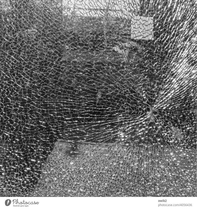 Zielscheibe Glasbruch Fensterscheibe gebrochen Zerbrochenes Fenster Menschenleer Strukturen & Formen Muster abstrakt Außenaufnahme Schwarzweißfoto Schaufenster