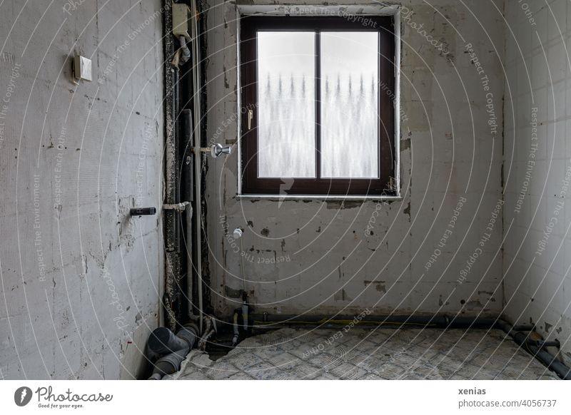 Sanierung: Altes Badezimmer mit Fenster, Steckdose, Leitungen und Abfluss, doch ohne Fliesen, Kacheln, Boden oder Heizung Renovierung Baustelle Raum Wände Rohr