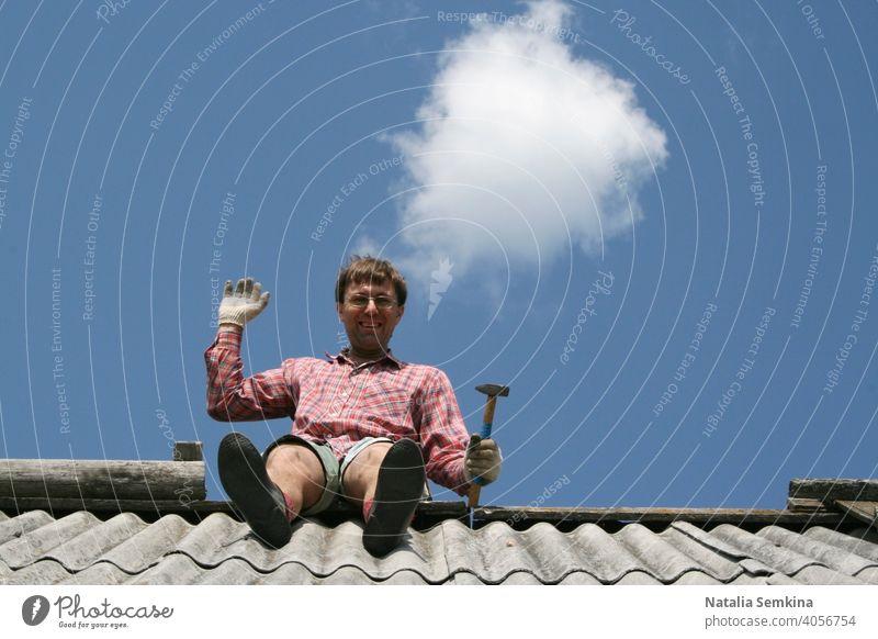 Fröhlicher Mann mit Hammer sitzt auf dem Dach eines Hauses, schaut in die Kamera und winkt mit der Hand vor dem Hintergrund eines klaren blauen Himmels mit einer runden Wolke. Unterer Winkel. Kopierraum für Text.