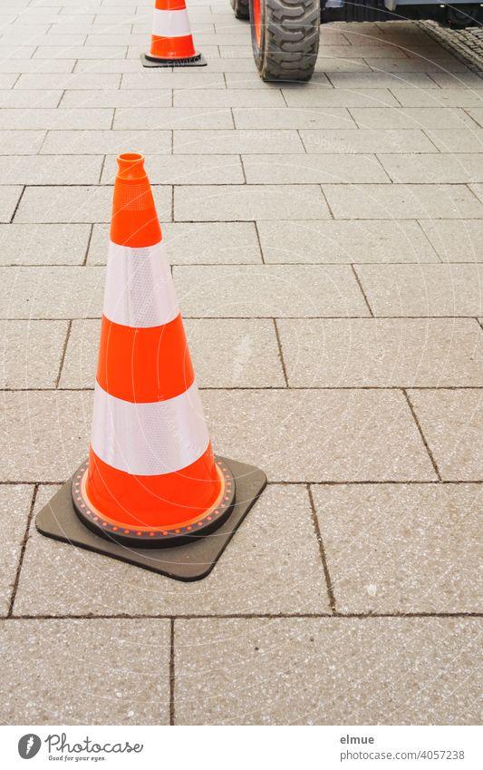 In einer Fußgängerzone sperren rot-weiße Pylone eine Baustelle ab - ein Teil des Baggers ist sichtbar / Bauarbeiten / Markierungshütchen / Sicherheit