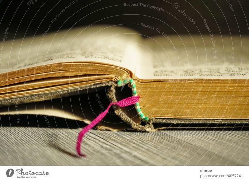 Seitenansicht eines aufgeschlagenen alten Buches mit pinkem Seitenfaden und Bucheinband / Bildung Bibel Lesezeichen offen Einband gold Holzboden Erinnerung