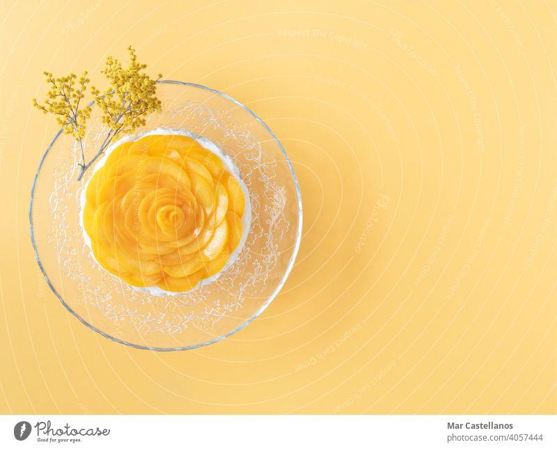 Drei-Milch-Dessert mit Pfirsichen auf gelbem Hintergrund verziert. Platz zum Kopieren. Ansicht von oben. cremig süß frisch Götterspeise Früchte melken